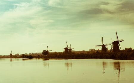 discolored: Landscape old quality of  Kinderdijk district popular tourist destination with its scenic fields, ponds, canls and windmills.