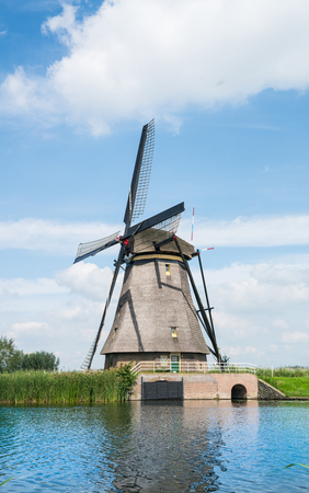 Traditional windmill on side of dyke in Dutch Kinderdijk district popular tourist destination with its scenic fields, ponds, canals Stock Photo