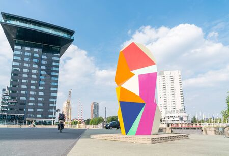 ROTTERDAM, HOLLAND -AUGUST 23, 2017; Multi-colored sculpture cubic sculpture, Marathon Image,  in Erasmuburg district with citys stunning modern architectural buildings forming backdrop Editöryel