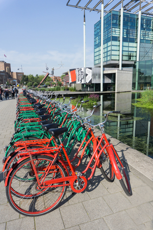 ROTTERDAM, HOLLAND- AUGUST 23, 2017; long row of red and green hire community use bicycles available for hire outside New Institute in Dutch city.