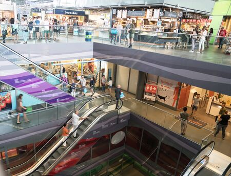 ROTTERDAM, HOLLAND - AUGUST 24, 2017; Escalator well with escalators down several floors , shops and people some blurred in movement in modern retail shopping mall.