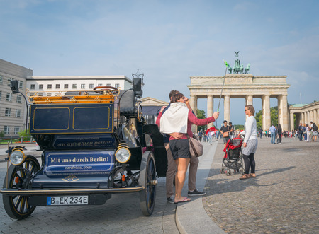 BERLIN, GERMANY - AUGUST 25, 2017; Neo-classical architectureof Barndenburg Gate in background selfie taking tourist by  replica carriage on street with sign