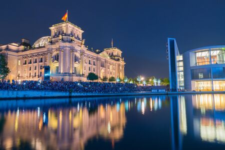 reflective: BERLIN, GERMANY - AUGUST 26, 2017;  Blue light tones over crowd seated along embankment in front Riechstag building for night light and picture show across River Spree illuminated buildings and reflected colors on calm water under dark sky.