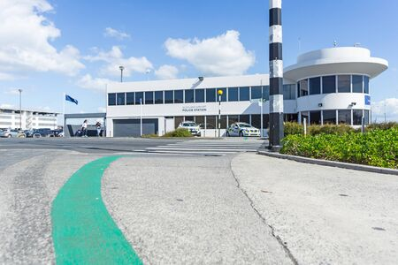 AUCKLAND, NEW ZEALAND - NOVEMBER 27, 2017; Green line sign on footpath showing way between international and domestic terminals with airport police building beyond black and white striped post