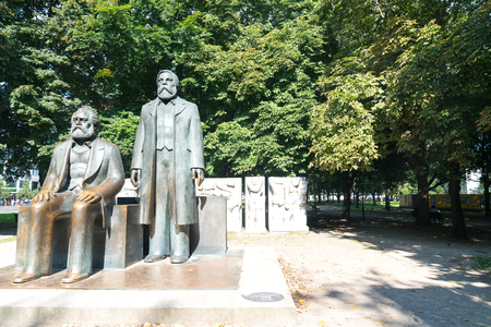 BERLIN, GERMANY -AUGUST 28, 2017; Statue of two men considered to be the fathers of socialism, Karl Marx and Friedrich Engels in park in Berlin.