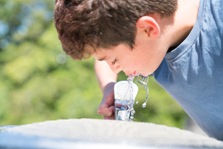 Boy at water fountain enjoying a cool drink refreshing fresh water on summer day. Stok Fotoğraf - 92856917