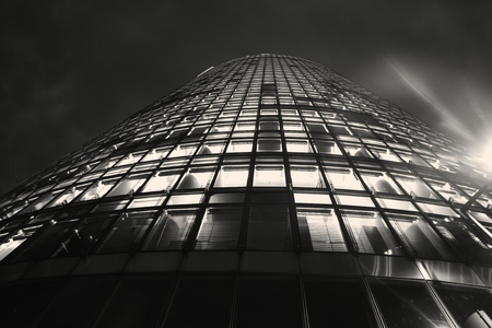 Tower of windows, high-rise modern office building from low angle with diminishing perspective risesinto dark sky.