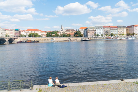 PRAGUE, CZECH REPUBLIC - AUGUST 29, 2017; Characteristic architecture and tourist boats alongside promenade across river with two young women tourists sitting on edge. Editorial
