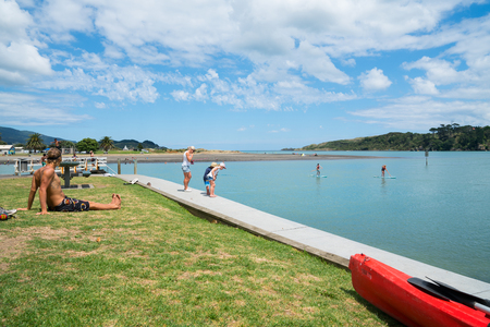 RAGLAN, NEW ZEALAND - JANUARY 14, 2018; Summer fun in Raglan children fishing with mother on harbour edge while man sits in sun.