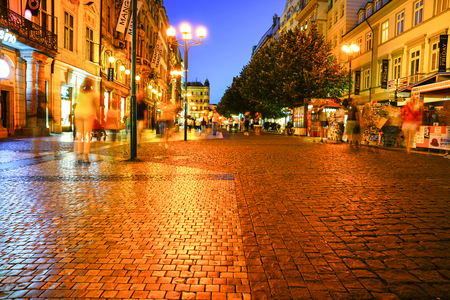 PRAGUE, CZECH REPUBLIC - AUGUST 30, 2017; shopping street passing people blurred in motion at night long exposure under glow of street lights.