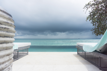 Poolside view to sea with dark storm clouds on horizon.