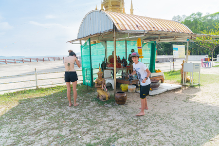 KO SAMUI, THAILAND - JANUARY, 25, 2018; Siblings are impressed by Buddhist shrine near beach on Bang Koa beach and enthusiastically take photos. 新聞圖片