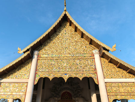 Traditional Asian architectural detail ornate facade of Thai Buddhist temple with curving roof line and curvy stenciled fascia and artistic gilt gable end.