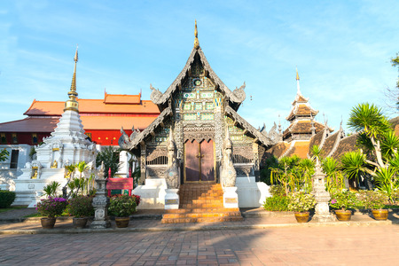 Ornate wooden temple facade red roof behind  surrounded by plants and white chedi in Chiang Mai, Thailand