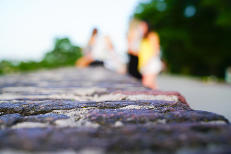 Abstract impressions of  small group people   defocused color blends beyond top of stonewall. Stock Photo