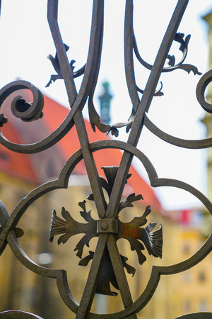 Wrought iron fence detail close-up with red roof and yellow building defocused impression behind.