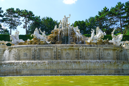 VIENNA,AUSTRIA - SEPTEMBER 4 2017; large water featurewhite statues  and fountain in grounds of Schonbrunn Imperial Palace and gardens constructed by Wilhelm Beyer