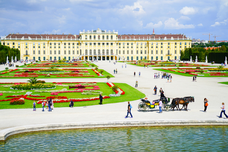 VIENNA,AUSTRIA - SEPTEMBER 4 2017; Tourists and horse and carriage in frontt Baroque architectural Schonbrunn imperial palace, one of the major tourist attractions in Vienna, Austria 報道画像