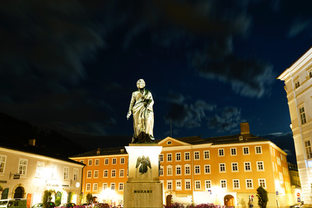 SALZBURG AUSTRIA - SEPTEMBER 7 2017; Statue Mozart in Square at night illumimnated and golden in color in Old Town.