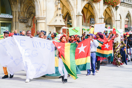 MUNICH, GERMANY - SEPTEMBER 8 2017; protestors carrying signs and Togo flags march through tourists in city central square below the gothic city hall.