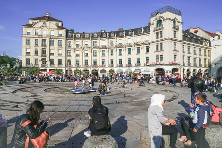 MUNICH GERMANY -SEPTEMBER 8, 2017; People and pigeons enjoy sunny day by famous Osram sign at the munich Karlsplatz (Stachus) on a busy day