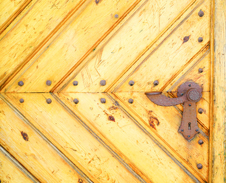 Section of old yellow door made of diagonal converging  wooden boards with rusty lever lock handle.