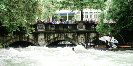 MUNICH GERMANY _ SEPTEMBER 11 2017; River surfers challenge raging rapids on Eisbach River in middle of European city while people stand on bridge watching and taking photos.