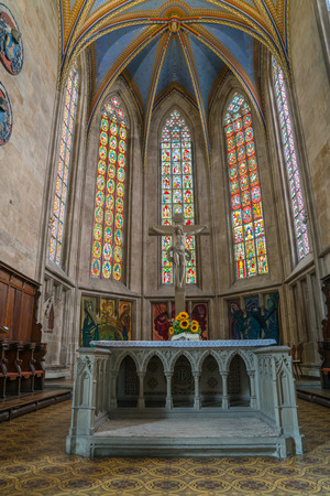 ESSLINGEN GERMANY - SEPTEMBER 13 2017; Alter with sunflowers  and stained glass windows under high beautiful vaulted ceiling inside traditionally architectural church in small German town.