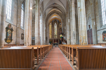 ESSLINGEN GERMANY - SEPTEMBER 13 2017; Long aisle between rows of pews to altar and stained glass windows inside traditional church Editorial