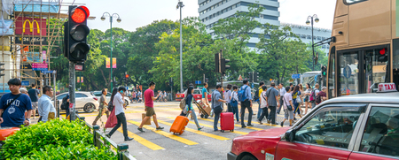 KOWLOON, HONG KONG - SEPTEMBER 18 2017; Typically Asian downtown city street  scene travelers with suitcases crossing on red light