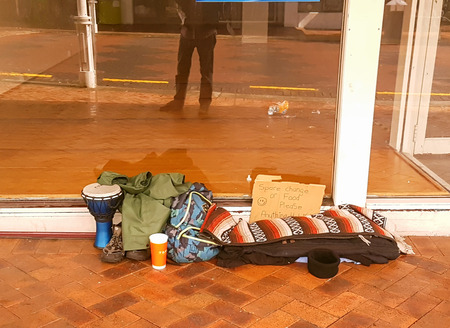 TAURANGA NEW ZEALAND - APRIL 16 2018; Beggars possessions left on footpath in front vacant shop with hand-written sign asking for spare change.