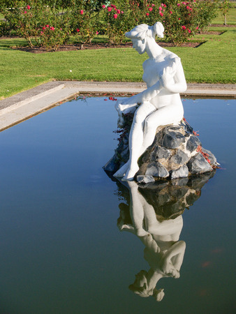 White lady statue reflected in calm water of pond sitting on rocks in middle Stock Photo