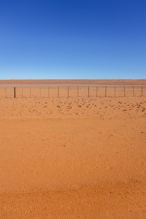Wide typically southern Namibia landscape ofAdeep iron rich orange soil under blue sky.