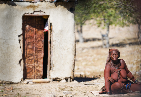 DAMARALAND NAMIBIA - MAY 21 2018; Tribal woman with traditional necklaces and adornments sits on mat outside hut.