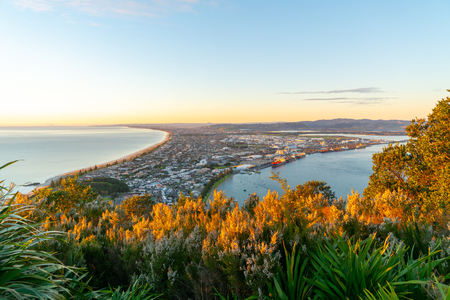 Glow of sunrise over sea and across town and harbor below and slopes of Mount Maunganui