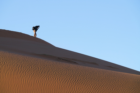SOSSUSVLEI, NAMIBIA - MAY 18 2018; Tourist photographer in distance on ridge on dunes of Hidden Vlei against blue sky  Sossusvlei Namibia Editorial