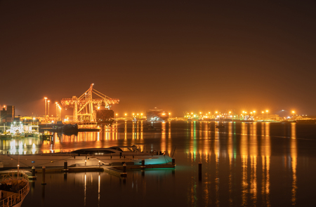 Glow and sparkle of port lights from Tauranga Harbour Bridge and surrounds illuminate night sky and harbour Stok Fotoğraf