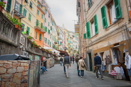 RIOMAGGIORE ITALY - APRIL 24 2011;  People passing along narrow lane between characteristic Mediterranean pastel colored multi-storeyed shops and apartments 新聞圖片
