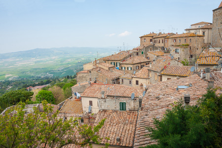 Tiered roofs over homes built up slope of hillside outside historic Italian town of Voltera