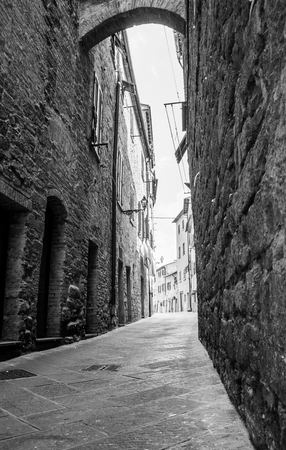 Rough stone walls in dark narrow laneway lined by high stone buildings leading bright street ahead.
