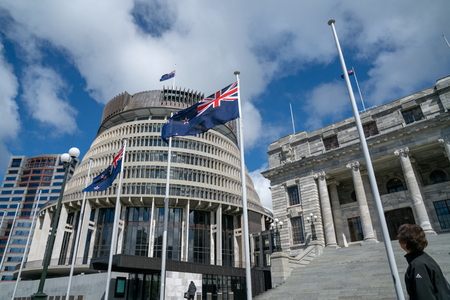 WELLINGTON NEW ZEALAND - OCTOBER 2 2018; Flags flutter in front New Zealand Government buildings, House neo classical style House of Parliament with Beehive behind.