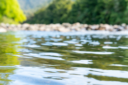 focus on water with defocused background of scenic rocky river bed of Anatoki River and lime green of new willow leaves and darker green of New Zealand bush surroundings.