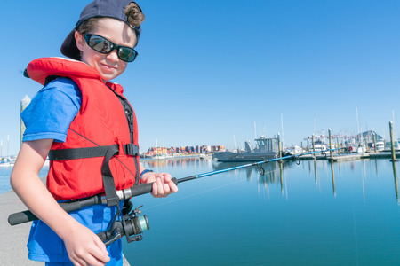 Boy stands on dock fishing from marina wearing red life-jacket and sunglasses looking up smiling Tauranga  New Zealand.