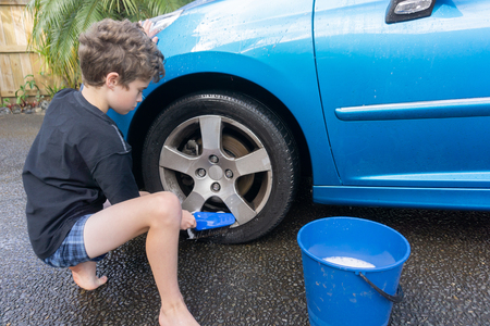 Boy earning pocket money cleaning blue compact car with hose, bucket of water and car brush cleaning wheels. Stockfoto