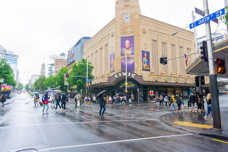 AUCKLAND NEW ZEALAND - DECEMBER 23 2018; People cross Queen Street and Wellesley Street intersection in front of historic Civic Theatre on wet day 版權商用圖片 - 117654223