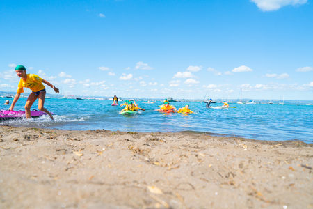 MOUNT MAUNGANUI NEW ZEALAND - FEBRUARY 10 2019:  Children carrying colorful paddle boards developing water confidence and skills by Mount Maunganui Surf Lifesaving Club Éditoriale