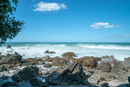 Waves smoothed by long exposure washing in around rocky foreshore at base of Mount Maunganui, Tauranga New Zealand Banco de Imagens