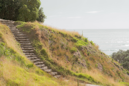 Vintage effect stone steps down track up Mount Maunganui with view beyond to Pacific Ocean at Tauranga New Zealand Banco de Imagens