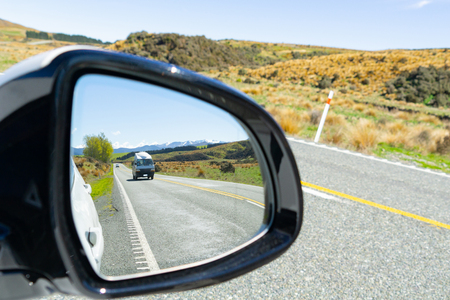 In rear view mirror view while driving the South Island New Zealand