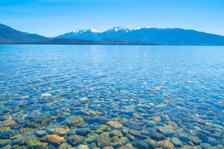 Stony lake edge of Lake Te Anau under clear blue sky